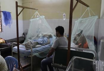 Patients lie under mosquito nets in a dengue fever ward at the hospital of Villa Elisa city near Asuncion