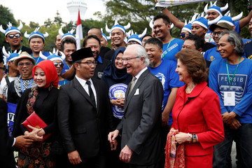 "King Carl XVI Gustaf of Sweden and Queen Silvia along with Ridwan Kamil, the mayor of Bandung, and his wife Atalia meet with supporters of the local football club Persib Bandung, who call themselves ""Vikings"" in Bandung, West Java"
