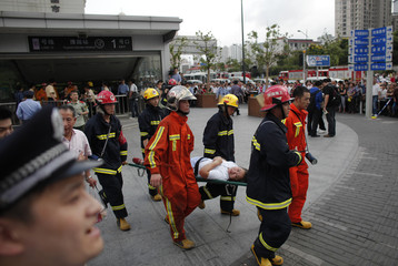 Rescue workers evacuate an injured woman outside Yu Yuan Garden station after a subway train collision in Shanghai