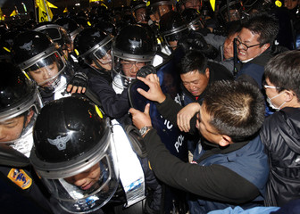 Protesters struggle with riot police as they try to march during a rally in central Seoul