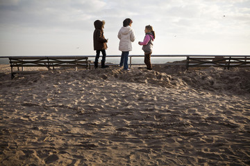 Girls stand on top of a pile of sand, washed onto the Brighton Beach boardwalk as a result of Hurricane Sandy, in Brooklyn, New York