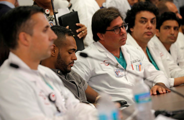 Gunshot survivor Angel Colon is surrounded by doctors as he listens to remarks at a news conference at the Orlando Regional Medical Center on the shooting at the Pulse gay nightclub in Orlando