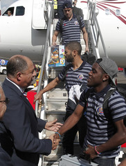 Costa Rica's President Solis greets Campbell of the Costa Rican national soccer team during their arrival at Juan Santamaria airport in Alajuela