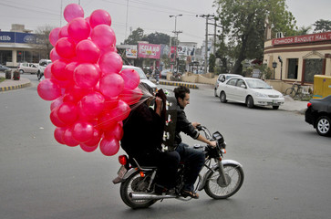 A man holds onto balloons while riding pillion on a motorcycle along a road on Valentine's Day in Lahore