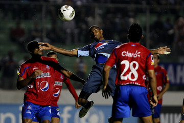 C.D Motagua's Jerry Bengtson jumps for the ball between C.S.D Municipal Yony Flores and Cristian Noriega during their CONCACAF Champions League soccer match in Tegucigapa