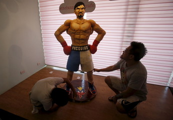 Baker Zach Yonson and an assistant put finishing touches on a life-size 70-kg chocolate cake of local boxing icon Pacquiao at a restaurant in Manila