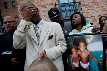 Mourners grieve at a vigil in honor of Edward and Edwin Bryant, twin brothers who were shot and killed in Chicago