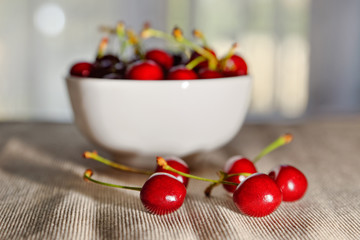 Cherries with full bowl in the background and shining light (selective focus)