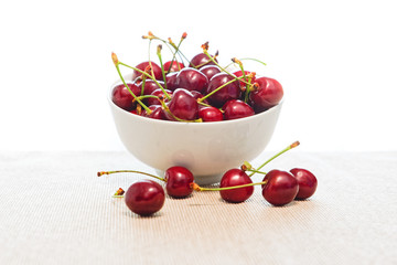 Wet cherries in a bowl with white background