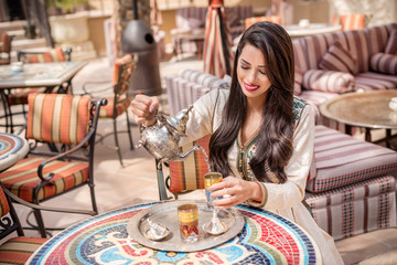 Arab Woman pouring tea. Middle Eastern arab woman in traditional  Moroccan dress drinking Moroccan Tea. Ramadan holiday theme.
