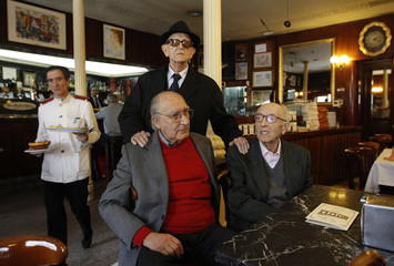 Members of a social gathering Arnedo, painter Canadas and writer Valenzuela sit at a table inside Spain's historic Cafe Gijon in Madrid