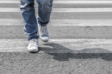 Man or woman is crossing the street on the crosswalk
