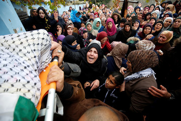 Relatives mourn as people carry the body of Palestinian Ahmed al-Remawi, who Palestinian Health Ministry said was shot and killed by Israeli forces on Sunday, during his funeral in the West Bank village of Beit Rima near Ramallah