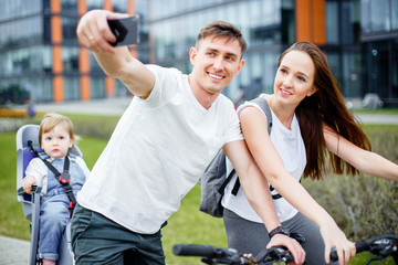 A happy family makes selfie on a smartphone while walking on bicycles in the summer.