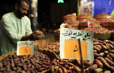 A shopkeeper checks his supplies of dates at a market ahead of the Islamic holy fasting month of Ramadan, in Cairo