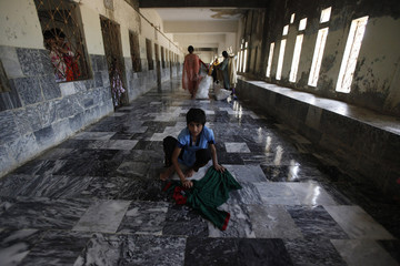Sherry, an abandoned child, cleans floor in halls of Edhi Home, a shelter for homeless and mentally ill women, in Karachi