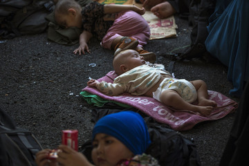 Children of suspected Uighurs from China's region of Xinjiang, rest on a ground inside a temporary shelter after they were detained near the Thailand-Malaysia border in Hat Yai