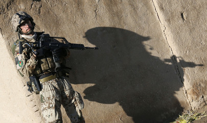 German Bundeswehr army soldier with the QRU casts a shadow as he stands near a wall during a joint patrol with the ANA in the village of Mulla Kehyl near Baghlan