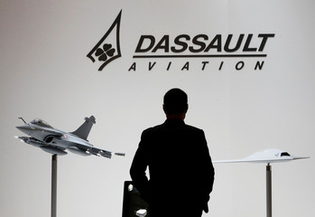 A file photo shows a visitor who looks at replicas of the fighter jet Rafale and Neuron on the Dassault booth during the EBACE in Geneva