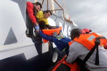 Lifeguards pull a migrant to the former fishing vessel Golfo Azzurro during a rescue operation, as lifeguards from the Spanish NGO Proactiva Open Arms rescue all 112 on aboard a drifting raft