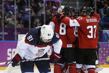 Canada celebrates their men's ice hockey semi-final win as Team USA's Kessel skates away at the Sochi 2014 Winter Olympic Games
