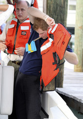Britain's Prince Harry puts on a lifejacket as he leaves after a tour of Harbour Island in Nassau