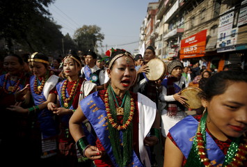 Gurung girls wearing traditional costumes dance while taking part in a New Year parade in Kathmandu