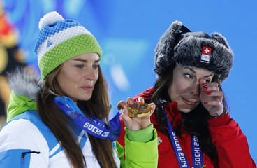 Joint gold medalists Switzerland's Gisin and Slovenia's Maze react during the medal ceremony for the women's alpine skiing downhill race at the Sochi 2014 Winter Olympic Games in Sochi