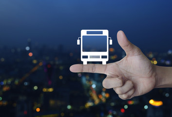 Bus flat icon on finger over blur colorful night light city tower, Business transportation service concept