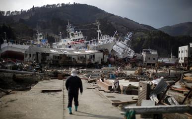 Man walks near damaged ships at an area destroyed by the 9.0 magnitude earthquake and tsunami in Kesennuma town in Miyagi prefecture