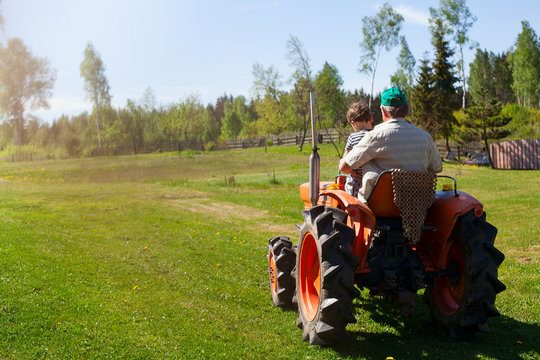 grandfather and his grandchild on a tractor