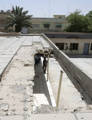 A man walks near where part of the roof has collapsed at al-Zahawi primary school in eastern Baghdad
