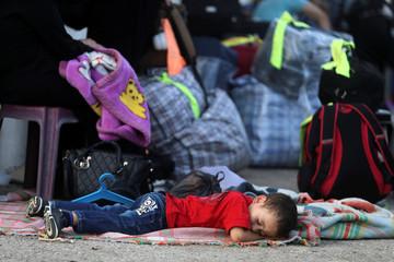 Palestinian boy sleeps as he waits with his family for a travel permit to cross into Egypt through the Rafah border crossing after it was opened by Egyptian authorities for humanitarian cases, in Rafah in the southern Gaza Strip