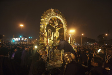"""A believer puts flowers arrangements on the """"Lord of Miracles"""" painting, Peru's most revered Catholic religious icon, in a major procession through central Lima"""