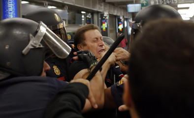 Spanish riot police detain a member of a railway picket during a strike at Atocha station in Madrid