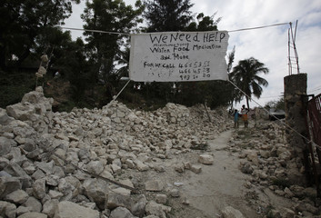 A sign that reads 'We need help - water medication and more' hangs outside a destroyed slum in the eartquake shaken Haitian capital of Port-au-Prince