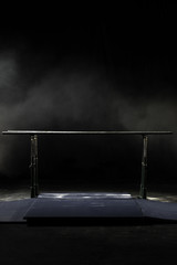 Closeup. Gymnastic parallel bars. Isolated on black background with fog, Vertical shot.