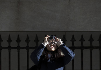 A tourist dressed for the cold photographs the New York Stock Exchange in New York's financial district