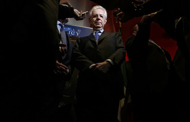 Members of the media surround Italian Prime Minister Mario Monti upon his arrival at the World Policy Conference in Cannes