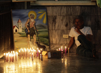 A worshipper smokes a cigar beside a painting in the shrine of Saint Lazarus in the town of Rincon