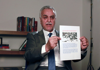 Iraq's fugitive Vice President Tareq al-Hashemi holds a document during an interview with Reuters in Istanbul