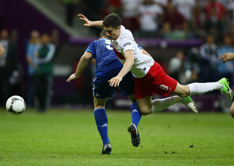 Poland's Lewandowski stumbles over Greece's Papadopoulos during their Euro 2012 Group A match at the National Stadium in Warsaw