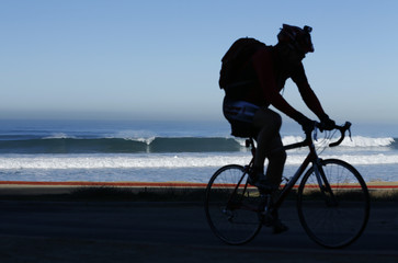 A cyclist climbs up a steep hill as he rides through Torrey Pines State Reserve in San Diego