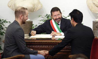 A gay couple, officially married outside Italy, sit while holding hands with each other in front of Rome's mayor Ignazio Marino during a ceremony for the recognition of their marriage in Rome