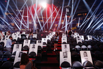 Journalists walk through cardboard cutouts showing where attendees will sit for the upcoming 2016 MTV VMA awards in New York