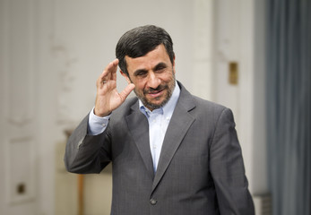 Iranian President Ahmadinejad waves to media as he attends for official meeting with Qatar's FM Adviser Mohammad al-Atiyeh in Tehran