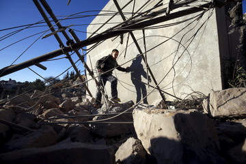 Palestinian boy walks at the rubble of a Palestinian house that was demolished by Israeli troops in the village of Silwad near Ramallah