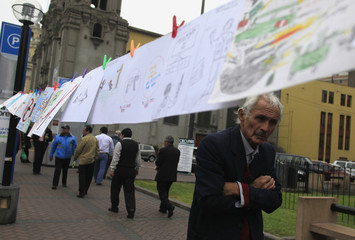 A man walks past drawings made by school children during a campaign to exchange weapon toys for educational toys to reduce violence in Lima