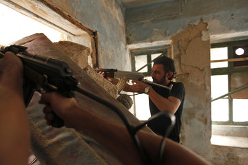 Free Syrian Army fighters aim weapons near Hanano Barracks, which is controlled by forces loyal to Syria's President Assad, in Aleppo