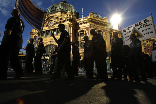 Veterans and their families are silhouetted against Flinders Street train station during the ANZAC Day march in Melbourne